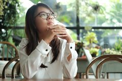Young woman holding mobile phone thinking and waiting for someon. Young asia woman holding mobile phone thinking and waiting for someone in coffee cafe. image Stock Photo