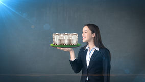 Young woman holding modern condominium on the open hand palm, over isolated studio background. Business concept. Portrait of young beautiful longhair woman royalty free stock photography