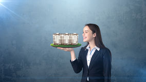 Young woman holding modern condominium on the open hand palm, over isolated studio background. Business concept. Portrait of young beautiful longhair woman royalty free stock images