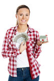 Young woman holding money and a house on hand. Royalty Free Stock Photography