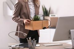 Young woman holding moving box with office stuff, closeup. Young woman holding moving box with office stuff indoors, closeup royalty free stock photo