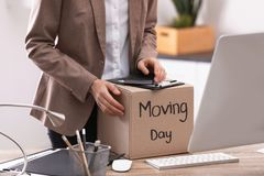 Young woman holding moving box with office stuff, closeup. Young woman holding moving box with office stuff indoors, closeup royalty free stock images