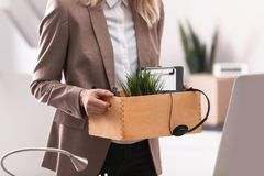 Young woman holding moving box with office stuff indoors. Closeup stock photo