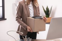 Young woman holding moving box with office stuff indoors. Closeup royalty free stock photo