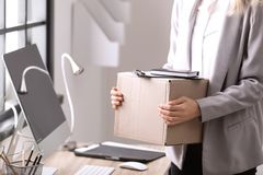 Young woman holding moving box with office stuff indoors. Closeup stock photography