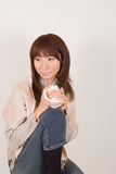 Young woman holding mug. Young Asian woman sitting with mug in hands Stock Images