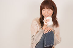 Young woman holding mug. Young Asian woman sitting with mug in hands Royalty Free Stock Images
