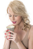 Young Woman Holding Mug of Coffee with Both Hands Looking into Mug Royalty Free Stock Photography