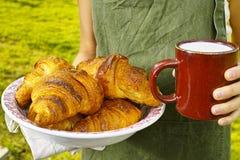 Young woman holding mug witn organic milk and fresh baked croiss Stock Photos