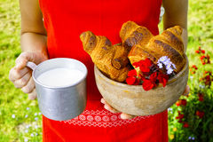 Young woman holding mug witn organic milk and fresh baked croiss Stock Images