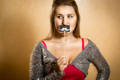 Young woman holding mustache drawn on decorative blackboard Royalty Free Stock Photos