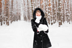 Young woman holding natural soft white snow in her hands to make a snowball, smiling during a cold winter day in the Stock Photography