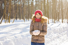 Young woman holding natural soft white snow in her hands to make a snowball, smiling during a cold winter day in the Stock Image