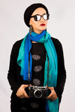 Young Woman holding old camera in hijab and colourful scarf royalty free stock image
