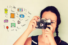 Young woman holding old camera and varius colorful sketches as her imagination Royalty Free Stock Image