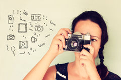 Young woman holding old camera and varius sketches as her imagination Stock Photos