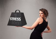 Young woman holding one ton of stress weight. Attractive young woman holding one ton of stress weight Royalty Free Stock Photo