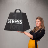 Young woman holding one ton of stress weight Royalty Free Stock Photo