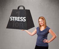 Young woman holding one ton of stress weight. Attractive young woman holding one ton of stress weight Royalty Free Stock Photos