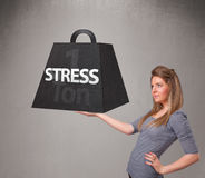 Young woman holding one ton of stress weight. Attractive young woman holding one ton of stress weight Stock Images