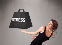 Young woman holding one ton of stress weight Royalty Free Stock Image