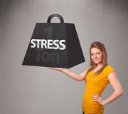 Young woman holding one ton of stress weight. Attractive young woman holding one ton of stress weight Stock Photo