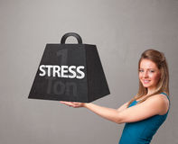 Young woman holding one ton of stress weight. Attractive young woman holding one ton of stress weight Stock Photos
