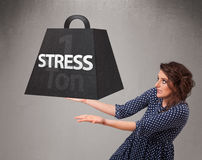 Young woman holding one ton of stress weight. Attractive young woman holding one ton of stress weight Royalty Free Stock Image