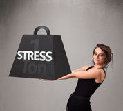 Young woman holding one ton of stress weight Stock Image