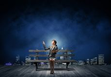 Young woman holding open book on bench stock photos