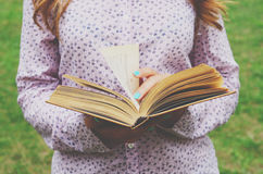 Young woman holding open book in her hands Royalty Free Stock Photos