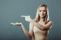 Young woman holding open palm showing copy space Royalty Free Stock Image