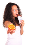 Young woman holding orange and chocolate. Isolated over white. I Stock Photos