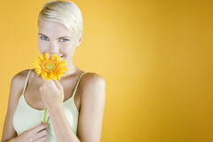 A Young Woman Holding An Orange Flower Royalty Free Stock Image