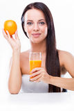 Young woman holding orange and orange juice Stock Image