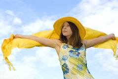 Young woman holding orange wrap against blue sky Royalty Free Stock Photos