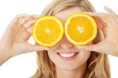 Young woman holding oranges on eyes Royalty Free Stock Image
