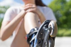Young woman holding painful knee after falling down. To ground with roller skates. Inline and rollerskates accident and pain. Injury to leg. Fracture and broken Royalty Free Stock Photography