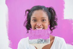 Young woman holding paintbrush with paint on her nose Royalty Free Stock Images