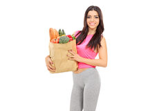 Young woman holding a paper bag full of groceries. Isolated on white background Royalty Free Stock Photo