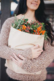 Young woman holding paper bag with ingredients for x-mas wreath Stock Photos