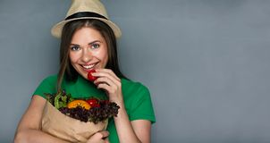 Young woman holding paper bag with vegetables Stock Photo