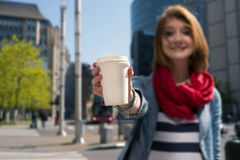 Young woman holding a paper cup and smiling. Young attractive woman holding a white paper cup and smiling against cityscape background Stock Images