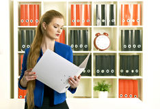 Young woman holding paper documents. Young business woman holding paper documents in office royalty free stock images