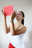 Young woman holding a paper in front of her. Young woman holding red paper Royalty Free Stock Photography
