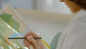 Young woman holding pencil over map, planning travel itinerary, holidaymaking. Stock footage