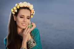 Young Woman Holding Perfume Bottle in Seaside Landscape Stock Image