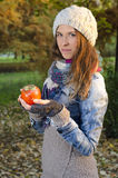 Young woman holding persimmon fruit in nature Stock Images