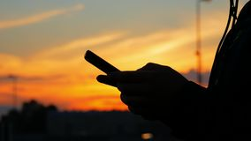 A young woman is holding a phone in her hands and is typing a message after jogging. Sunset. Silhouette stock video