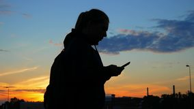 A young woman is holding a phone in her hands and is typing a message after jogging. Sunset. Silhouette. A young woman is holding a phone in her hands and is stock video footage
